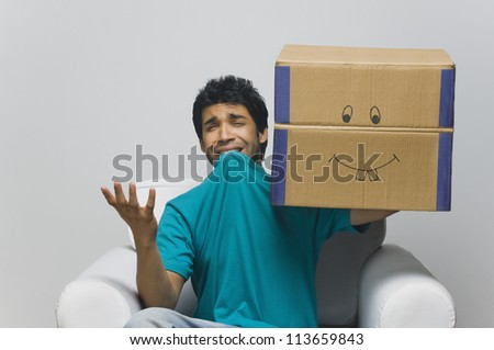 Man holding a cardboard box and looking sad