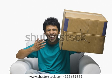 Man holding a cardboard box with a smiley face and laughing