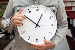 man holding a clock, concept time change for winter time or standard time