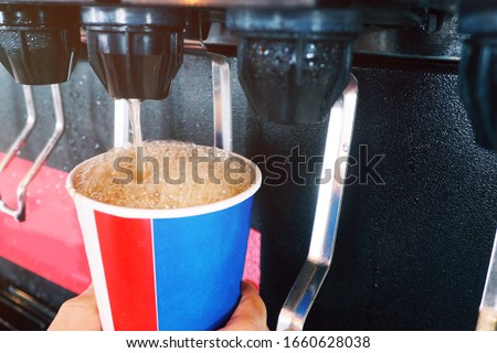 Man holding a cup at soft drink self service machine pouring cola fizzy drink at a restaurant. Soft drinks are popular for refreshment but consuming too much can cause high level of sugar in blood