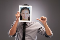 Man holding a digital portrait of a woman on the tablet in front of his head
