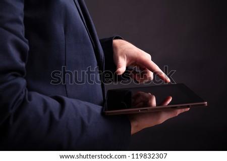 Man holding a digital tablet on black background