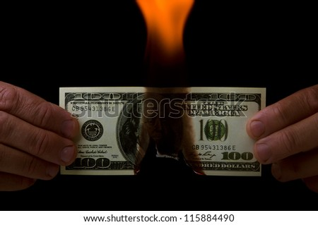 man holding a dollar in flame on black background