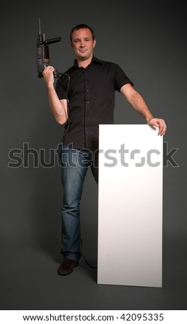 Man holding a drill and a vertical white board