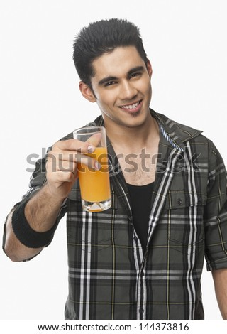 Man holding a glass of juice and smiling #144373816
