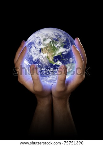 Man holding a glowing planet earth in his hands. Earth image provided by NASA.