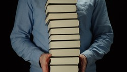 Man Holding A High Pile Of Thick Black Books In His Hands