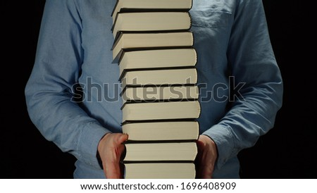 Man Holding A High Pile Of Thick Black Books In His Hands ストックフォト ©