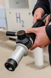 Man holding a hydrogen fuel filler nozzle for refueling hydrogen powered vehicles