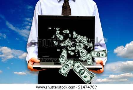man holding a laptop with money coming out of it