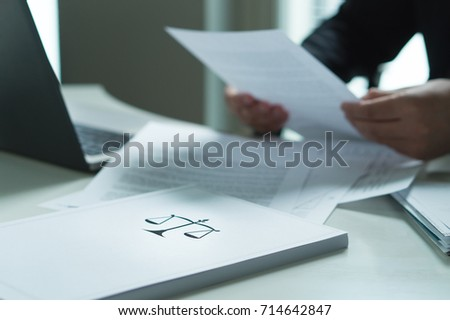 Man holding a legal document in hand. Lawyer holding law paper in office. Scale and justice symbol. #714642847