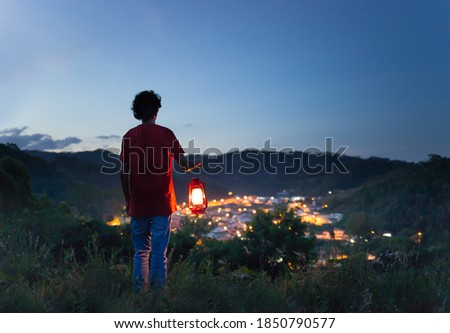 Man holding a lit kerosene lamp on the top of the mountain and watching the city lights in the valley. Electric power. Foto d'archivio ©