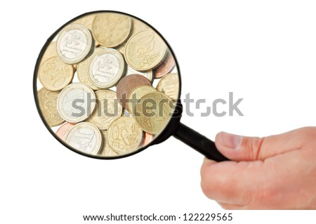 Man holding a magnifying glass above coins