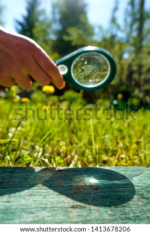 Man holding a magnifying glass making fire, focused on wood.