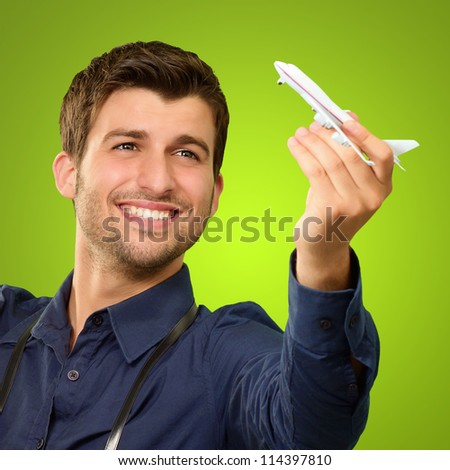 Man Holding A Miniature Airplane On Green Background