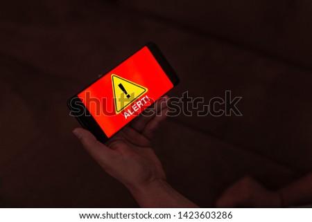 man holding a mobile phone showing alert message - Alert Caution Risk Danger Attention Concept #1423603286