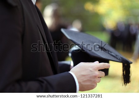 Man holding a mortar board in focus on a autumn day in Oxford