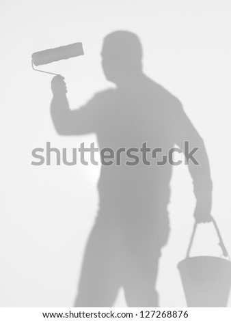man holding a paint roller with one hand and a bucket with the other one, behind a diffuse surface