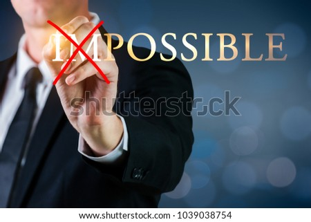 Man holding a pen to cross impossible possible word