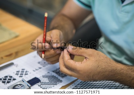 Man holding a piece of fabric and checked tissue for quality control. Textile industry concept background image.