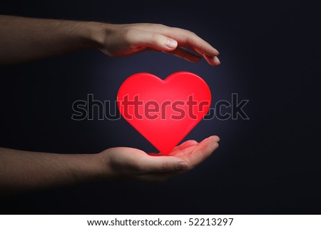 Man holding a red glowing heart in his hands #52213297