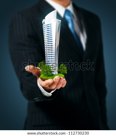 Man holding a skyscraper  in hand - stock photo