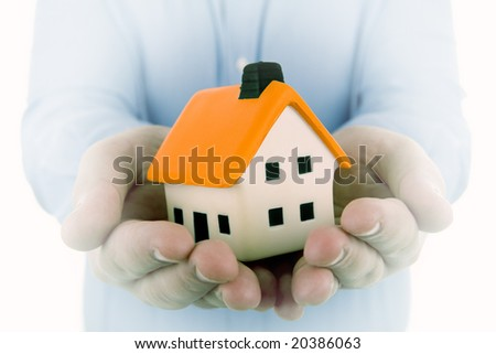 man holding a small house in his hands with dream effect to emphasize the house