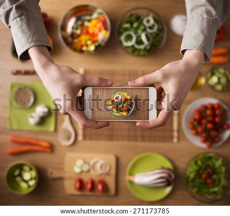Man holding a smart phone hands close up, kitchen table worktop on background with fresh vegetables and utensils