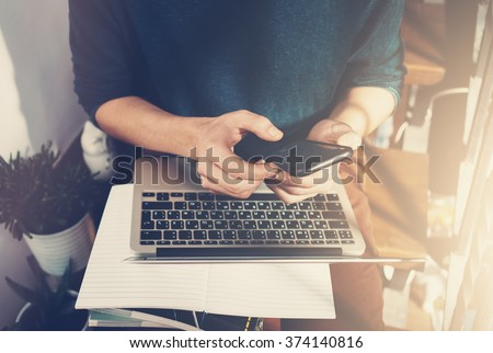 Man holding a smartphone in hands and writes the message. Generic design laptop is on his knees. Sunlights
