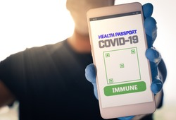 Man holding a smartphone with Immune digital passport for covid-19. Suitable for immunity passport app on the phone to monitorize the population movements at the end of the lockdown