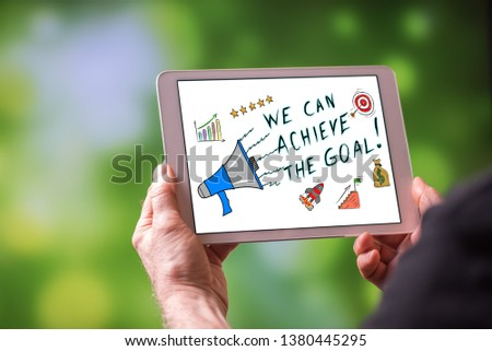 Man holding a tablet showing goal achievement concept