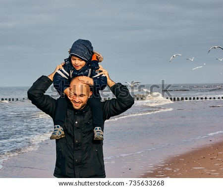 Man holding a toddler boy on his shoulder at a beach on a cloudy day on October 2017 in Sarbinowo, Poland                          #735633268