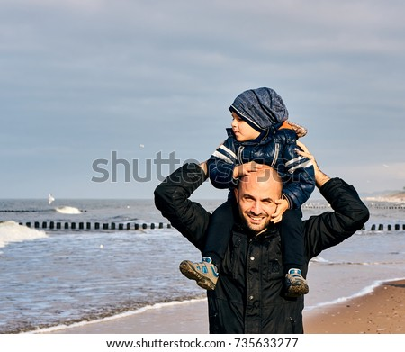 Man holding a toddler boy on his shoulder at a beach on a cloudy day on October 2017 in Sarbinowo, Poland                          #735633277