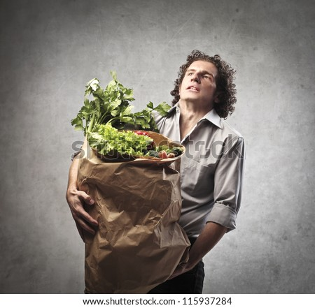 Man holding a very heavy bag full of vegetables