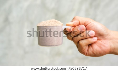 Man holding a whey protein on gray background.