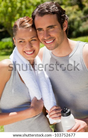 Man holding a white sports bottle smiling with a woman who is holding a towel