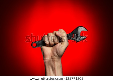 man holding adjustable wrench over red background
