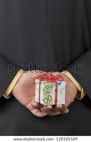 Man holding an expensive gift box wrapped in euro banknotes behind his back