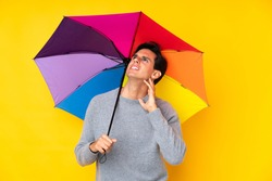 Man holding an umbrella over isolated yellow background thinking an idea