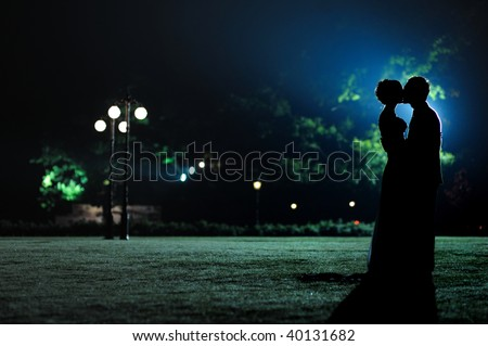 Man holding and kissing woman silhouettes in the evening park