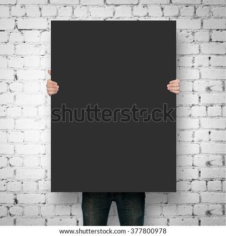 Man holding black poster mockup over brick wall #377800978