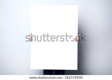 Man holding blank poster on grey background