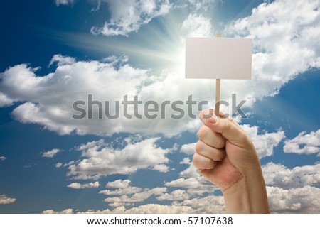 Man Holding Blank Sign Over Dramatic Clouds and Blue Sky with Sun Rays - Ready For Your Own Message on Sign and Over Clouds.