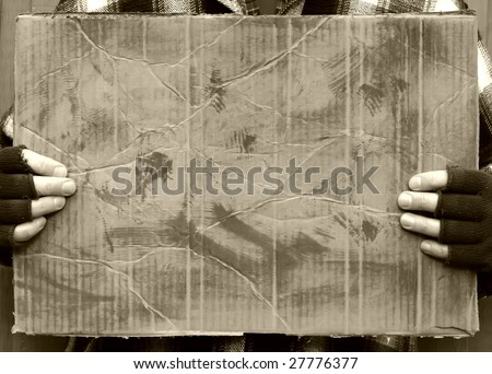 man holding blank worn out cardboard sign