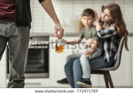 Man holding bottle of alcohol while wife hugging their son on background