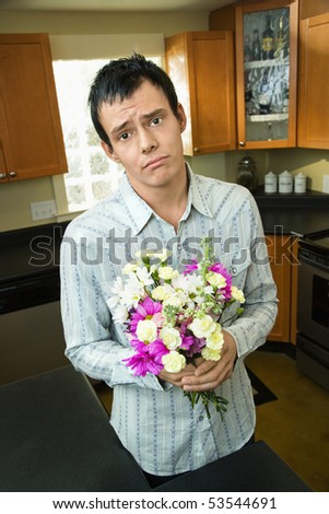 Man holding bouquet of flowers looking sorry and asking forgiveness. - stock photo