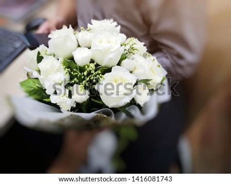 man holding bouquet of white roses at office. boyfriend surprise boyfriend with flower in valentine's day. celebrate anniversary, love & relationship concept. #1416081743