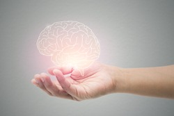 Man holding brain illustration against gray wall background. Concept with mental health protection and care.