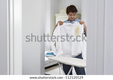 Man holding burned shirt by ironing board