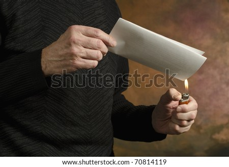 man holding butane lighter to folded document - stock photo